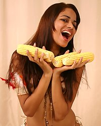 Native indian girl Polliana eating and playing with corn on the cob for Thanksgiving.